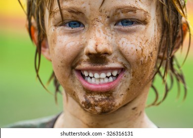 Cute, happy child with very dirty face after playing sports
