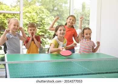 Cute happy children playing ping pong indoors