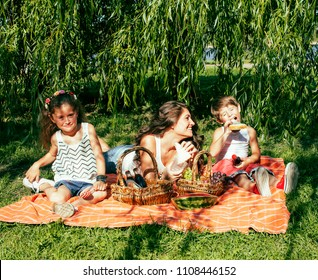 cute happy family on picnic laying on green grass mother and kids, warm summer vacations