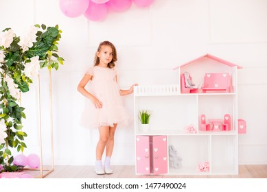 Cute happy girl in a beautiful dress at home plays with a dollhouse and toys