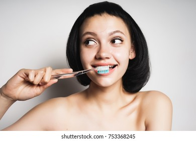 cute happy girl with black hair brushes teeth with toothbrush
