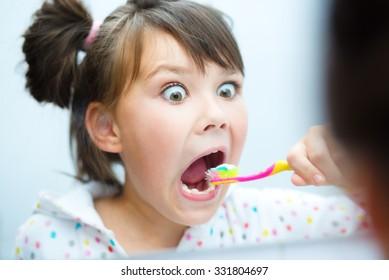 Cute happy girl brushes her teeth in the bathroom