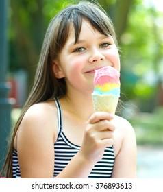 Cute happy girl is eating ice-cream