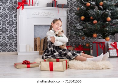 Cute happy girl hug toy rabbit, christmas present on holiday morning in beautiful room. Female child got Xmas gift near decorated fir tree and fireplace. Winter holidays concept
