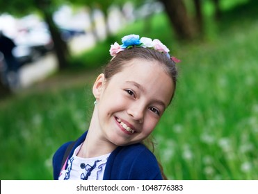 Cute Happy Girl Outdoors enjoying nature. Beautiful Teenage girl with long hair smiling at sunny day.