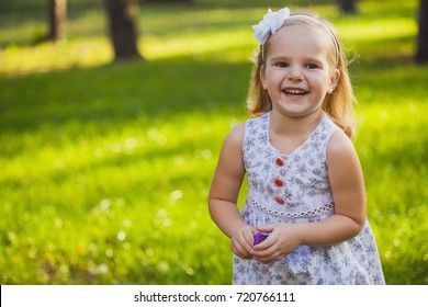 cute, happy girl playing in the sunny summer park
