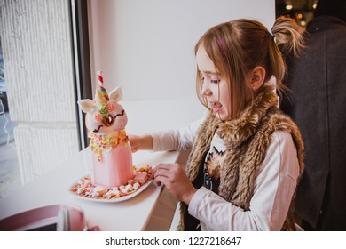 Cute happy girl in trendy clothes is drinking a pink milkshake from a tube decorated by a donut in the form of a unicorn, candies in cafe with light in the background