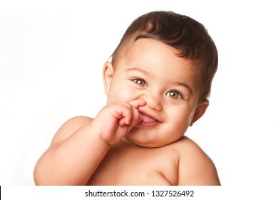 Cute happy innocent baby infant with big light green eyes picking nose, childhood concept, on white.