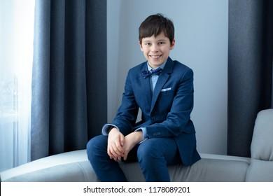 Cute happy junior boy in dark classic suit outdoors. Children portrait. Stylish kid in suit