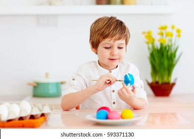 cute happy kid, boy painting easter eggs at the kitchen desk