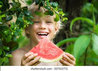Cute happy kid eating watermelon in summertime in the garden