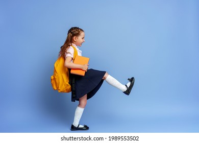 Cute happy kid in uniform. raises his leg high and runs on purple background. child with backpack. little girl is ready for school. Dynamic images that go back to conceptual school. holidays begin.