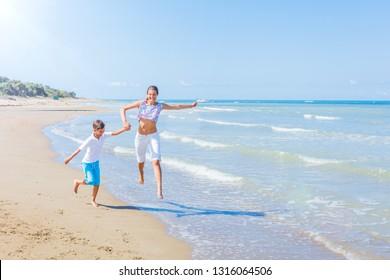 Cute happy kids - girl and boy having fun on tropical beach