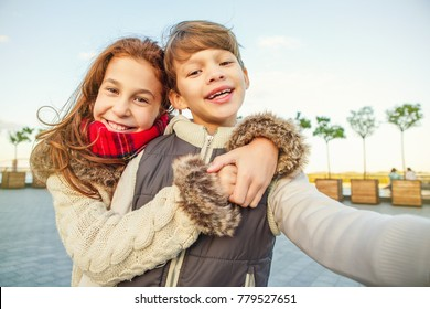 Cute happy kids taking a selfie outdoors together brother sister embracing hugging smile toothy excitement travelling family siblings recreation seasonal joy fun communication interaction carefree