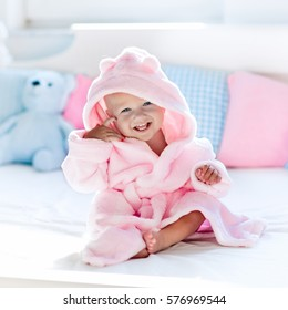 Cute happy laughing baby in soft bathrobe after bath playing on white bed with blue and pink pillows in sunny kids room. Child in clean and dry towel. Wash, infant hygiene, health and skin care