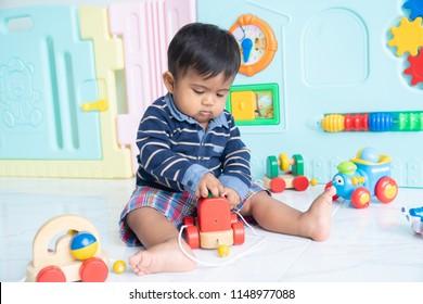 Cute happy little asian boy lying play wooden toy car