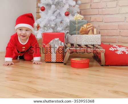 198d359cccb6 cute happy little baby boy in Santa suit and old vintage sled with gifts  near Christmas