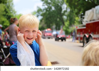 A cute, happy little boy child is covering his ears from the loud fire Truck sirens at a small town American Parade.