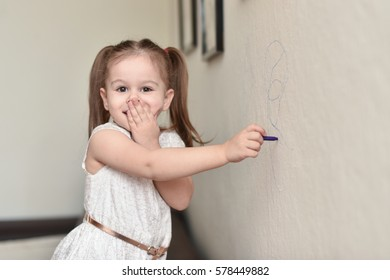 Cute happy little child writing on wall with surprised face