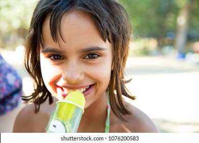 Cute and happy little girl eating a lime ice cream after siwimming in the pool