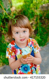 Cute and happy little girl eating ice cream outside
