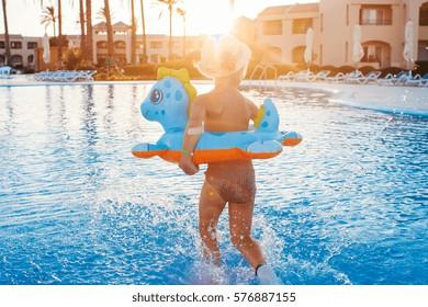 Cute happy little girl having fun in swimming pool