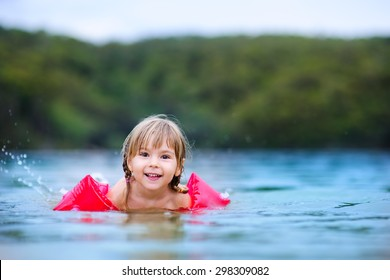 cute happy little girl learning swim at the ocean with floatation device