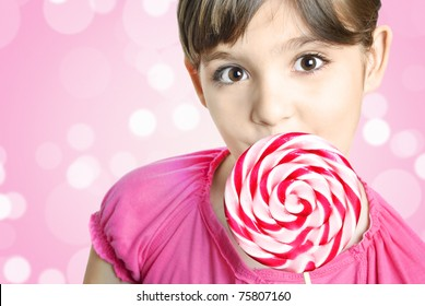 Cute happy little girl with lollipop candy in front of colorful pink background with copyspace