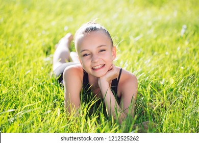 cute happy little girl lying on the grass