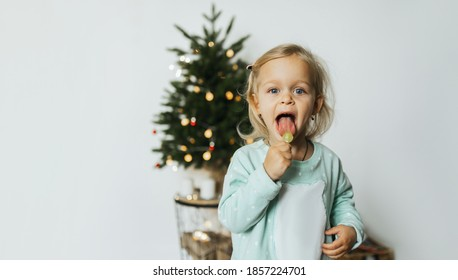 A cute happy little girl in pajamas  with sugar lollipop. merry christmas and happy new year concept. Space for text. Family cozy moments.