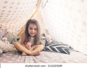 Cute happy little girl playing with toys and dreaming in teepee and bed. Close up photo of happy child.