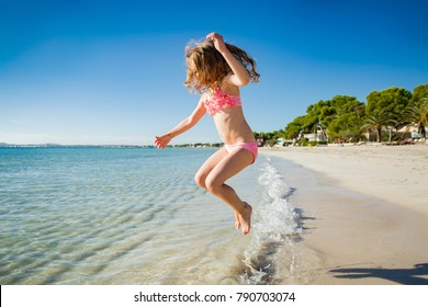 Cute happy little girl running along the beach in swimming suit, jumping over waves. Beautiful summer sunny day, blue sea, picturesque landscape. Majorca, Spain
