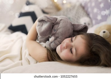 Cute happy little girl sleeping and dreaming in and bed hugging her toy. Close up photo of sleeping child.