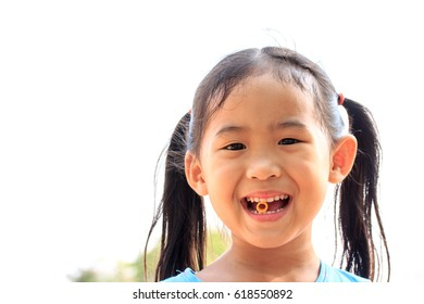 A cute happy little girl smiling and eating snack