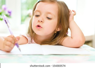 cute happy little girl writing something in her notebook