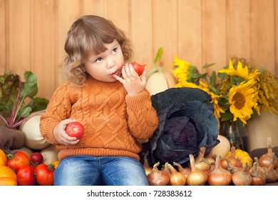 Cute happy little kid with different vegetable harvest, eating tomato, autumn, wood rustic background, countryside