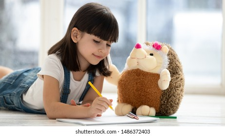 Cute happy little kid girl playing drawing pencils with fluffy hedgehog lying on warm heated floor at home, funny creative preschool small child teaching stuffed toy coloring picture having fun alone