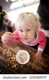 A cute and happy little toddler girl is playing and making a mess as she eats her breakfast cereal.