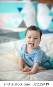 Cute happy mixed race Asian Caucasian baby boy plays joyfully on a bed at home