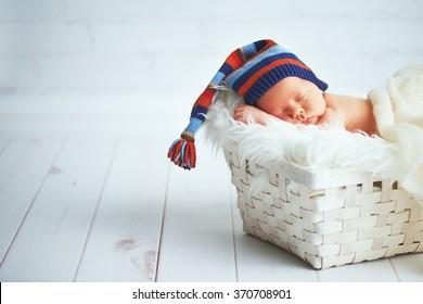 Cute happy newborn baby in a blue knit cap sleeping in a basket