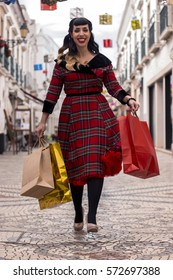 Cute and happy pinup girl goes shopping in Christmas on the streets of Faro, Portugal.