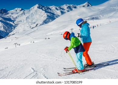Cute happy skier boy with his mother having fun in a winter ski resort.