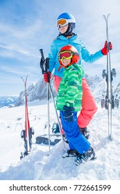 Cute happy skier boy with his mother in a winter ski resort.
