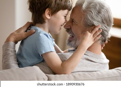 Cute happy small preschooler boy child hug cuddle smiling elderly Caucasian grandfather show love and care. Little 7s kid have fun relax with overjoyed senior grandparent at home. Gratitude concept.