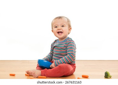 Cute, happy, smiling baby playing with food, sitting on the floor with a white background. Ethnically ambiguous infant in bright clothing holding blue bowl with carrots and broccoli. Happy and healthy