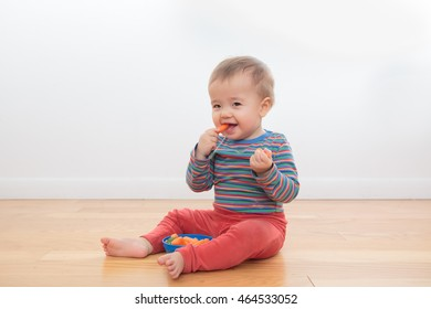 Cute, happy, smiling baby playing with food, sitting on the floor with a white background. Ethnically ambiguous infant in bright clothing, eating carrots and broccoli from a blue bowl. Happy, healthy.