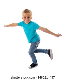 CUTE HAPPY SMILING BOY STANDING ON ONE LEG AND MAKING LIKE FLYING WHILE HOLDING BALANCE WITH OUTSTRETCHED HANDS ISOLATED ON WHITE BACKGROUND