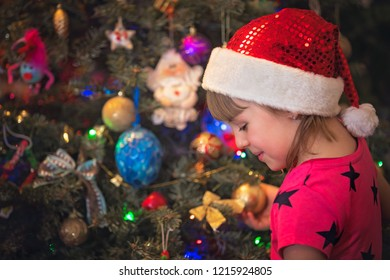 Cute happy and smiling Caucasian Christmas girl putting the decorations on the Christmas tree