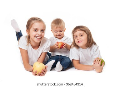 Cute happy smiling family of two sisters with junior brother posing with fruit apples