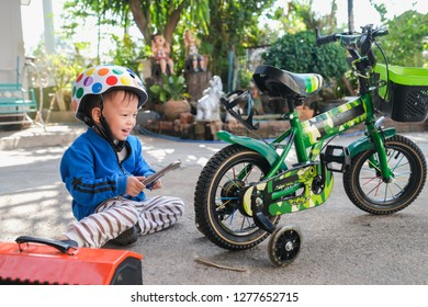 Cute happy smiling little Asian 2 - 3 years old toddler boy child wearing safety helmet repairing bicycle wheel with spanner (holding wrench) in sunny summer day outdoor, kid having fun with his bike
